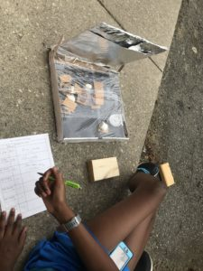 Youth participant logging observations while baking S'mores to test solar cooker.
